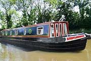 A narrowboat stops at a canalside pub